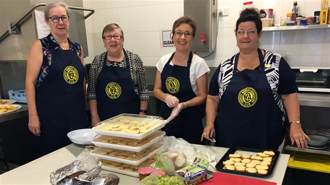 Photo of members of Cessnock Country Women's Association (CWA) wearing CWA aprons and standing in front of a table with food on it