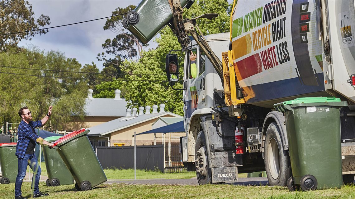 Image of man waiting to have his waste collected by garbage truck