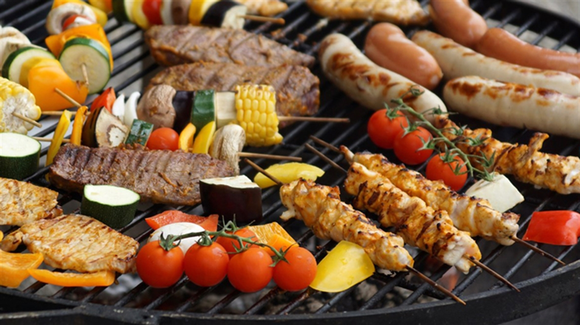 Photo of steaks, sausages, tomatoes and kebobs cooking on a barbecue